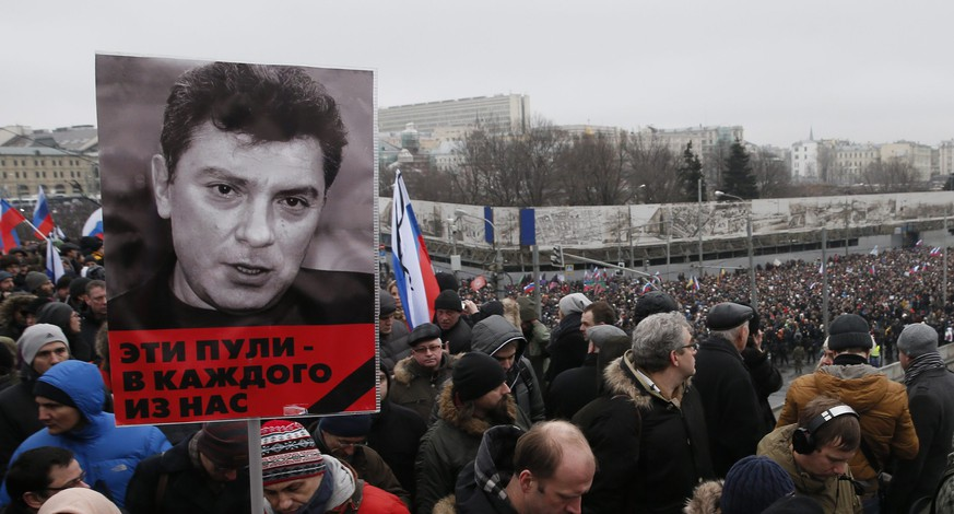 epa04643232 A portrait of murdered Russian opposition veteran leader Boris Nemtsov is held by a member of the march, in his memory, in central Moscow, Russia, 01 March 2015. Opposition holds a march in the memory of murdered Kremlin critic Boris Nemtsov, having replaced the scheduled on 01 March opposition rally 'Vesna' (Spring). Boris Nemtsov, one of the organizers of the Vesna rally, was shot dead late in the evening of 27 February while walking on the Bolshoy Kammeny bridge near the Kremlin.  EPA/SERGEI ILNITSKY
