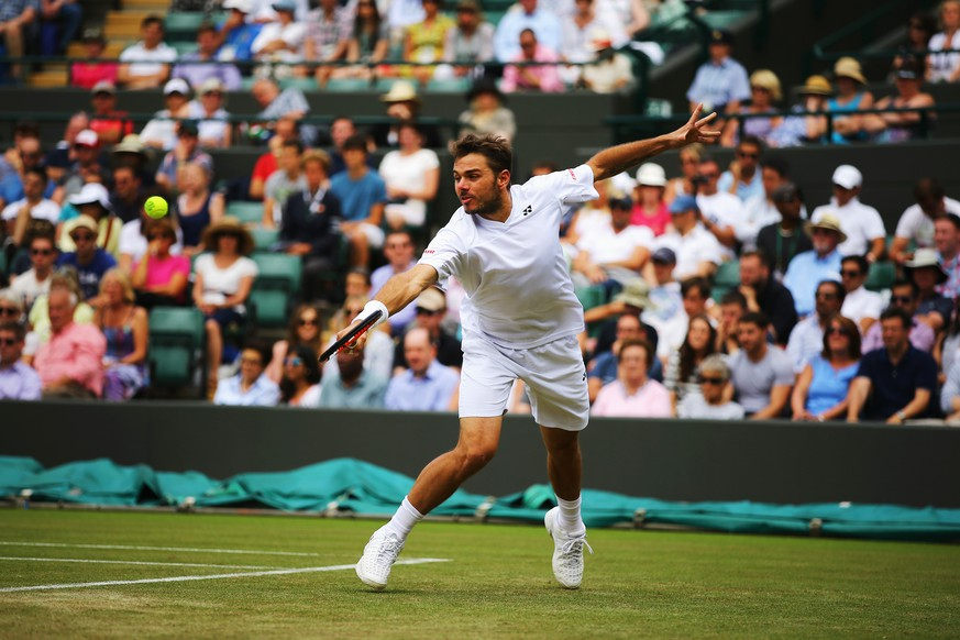 LONDON, ENGLAND - JUNE 26:  Stan Wawrinka of Switzerland returns the ball during his Gentlemen's Singles second round match against Yen-Hsun Lu of Chinese Taipei on day four of the Wimbledon Lawn Tennis Championships at the All England Lawn Tennis and Croquet Club at Wimbledon on June 26, 2014 in London, England.  (Photo by Al Bello/Getty Images)