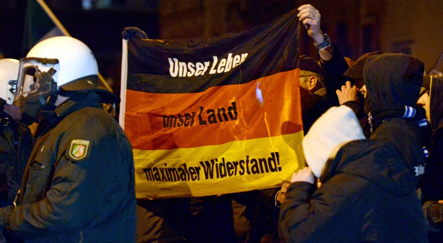 epa04569818 Anhänger der islamkritischen Bewegung Members of the regional 'Pegida NRW' anti-Islam movement hold a German natiuonal flag with the slogan: 'Our Life - Our Country - Maximum Restistance' as they gather for a demonstration in Duisburg, Germany, 19 January 2015. 'Pegida NRW' is a regional offshoot of the Islam-critical 'Pegida' movement (Patriotic Europeans against the Islamization of the West) in the German North Rhine-Westphalia state.  EPA/CAROLINE SEIDEL