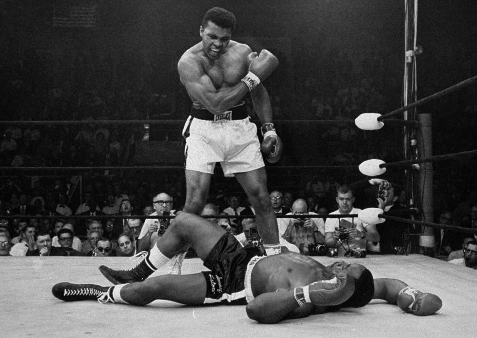 ADVANCE FOR USE SUNDAY, FEB. 23, 2014 AND THEREAFTER - FILE - In this May 25, 1965 file photo, heavyweight champion Muhammad Ali stands over fallen challenger Sonny Liston, shortly after dropping Liston with a short hard right to the jaw in Lewiston, Maine. In 1964 he dropped the name Cassius Clay and adopted his Muslim name. (AP Photo/John Rooney)