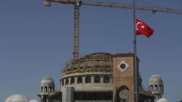 A Turkish flag flies half-mast in main Istanbul's Taksim Square, backdropped by a mosque under construction, Tuesday, May 15, 2018. Turkey has lowered flags to half-mast to mark three days of mourning for the Palestinians killed and wounded along the Gaza border as they protested the Gaza blockade and the relocation of the U.S. embassy to Jerusalem. (AP Photo/Emrah Gurel)