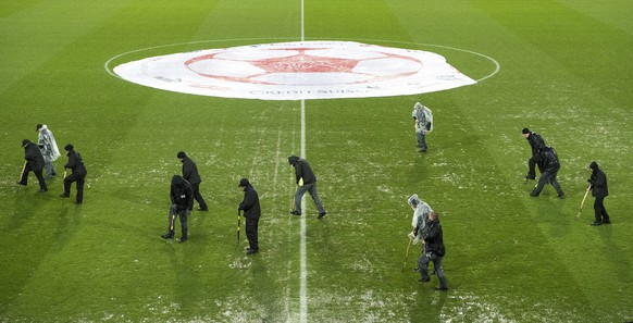 epa06324884 Staff members work under heavy rain to evacuate water from the field, prior to the 2018 Fifa World Cup play-offs second leg soccer match Switzerland against Northern Ireland at the St. Jakob-Park stadium in Basel, Switzerland, 12 November 2017.  EPA/JEAN-CHRISTOPHE BOTT