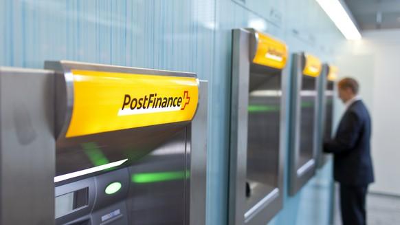 ARCHIVBILD ZUM ABBAU VON 500 STELLEN BEI POSTFINANCE --- [GESTELLTE AUFNAHME/SYMBOLBILD] Ein Mann bezieht am Postomat der Poststelle am Baerenplatz in Bern Geld, aufgenommen am 16. Juli 2012. (KEYSTONE/Gaetan Bally)