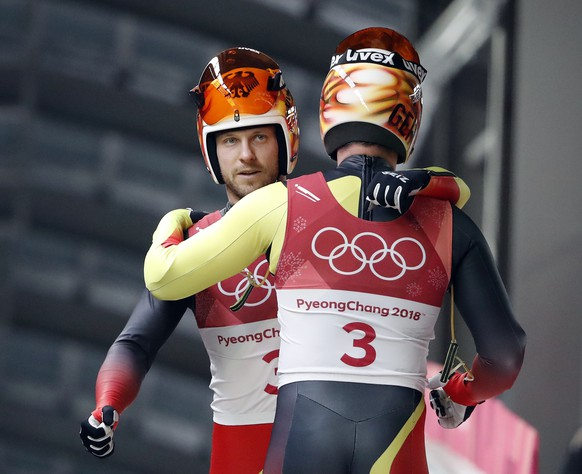 Tobias Arlt and Tobias Wendl of Germany hug in the finish area after their first run during the men's doubles luge final at the 2018 Winter Olympics in Pyeongchang, South Korea, Wednesday, Feb. 14, 2018. (AP Photo/Andy Wong)