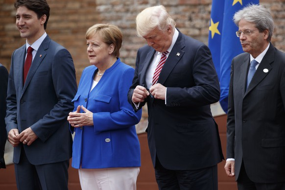 President Donald Trump adjusts his jacket during a family photo with G7 leaders at the Ancient Greek Theater of Taormina, Friday, May 26, 2017, in Taormina, Italy. From left are, Canadian Prime Minister Justin Trudeau, German Chancellor Angela Merkel, Trump, and Italian Prime Minister Paolo Gentiloni. (AP Photo/Evan Vucci)