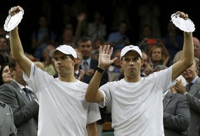 Bob Bryan of the U.S. (R) and Mike Bryan of the U.S. hold their runners-up trophies after being defeated by Vasek Pospisil of Canada and Jack Sock of the U.S. in their men's doubles final tennis match at the Wimbledon Tennis Championships, in London July 5, 2014.              REUTERS/Suzanne Plunkett (BRITAIN  - Tags: SPORT TENNIS)