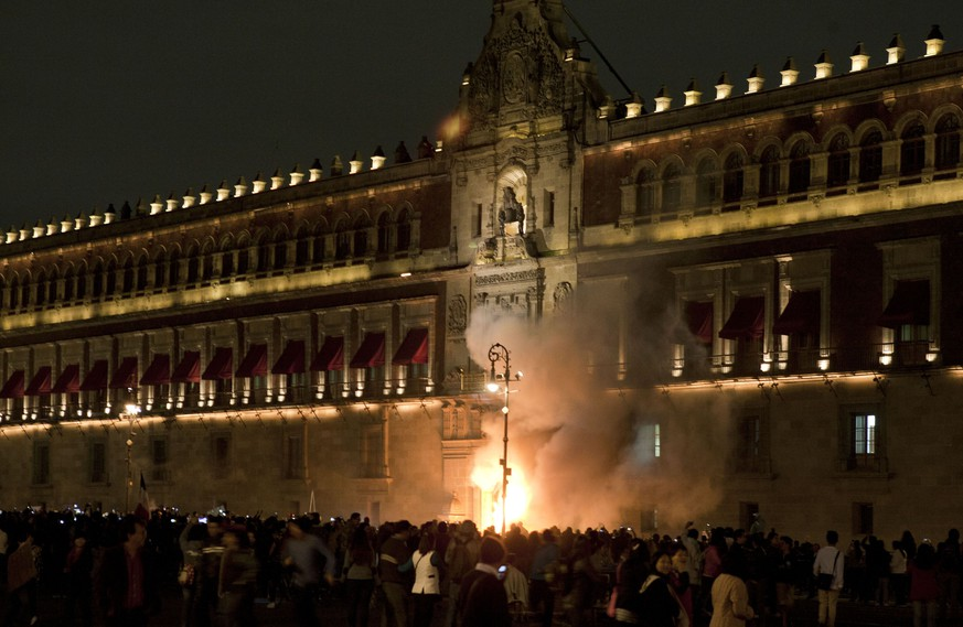 Demostrators set fire the door of the main entrance of te Mexican National Palace during a demostration in Mexico City on November 8, 2014, demanding justice from the Mexican goverment in the massacre of 43 missing students. Mexico was confronted with one of the grisliest massacres in years of drug violence after gang suspects confessed to slaughtering the students and dumping their charred remains in a river. The case has revulsed Mexico since gang-linked police attacked the young men in the southern state of Guerrero on September 26, in a night of violence that left six people dead and the 43 missing. AFP PHOTO/Omar Torres