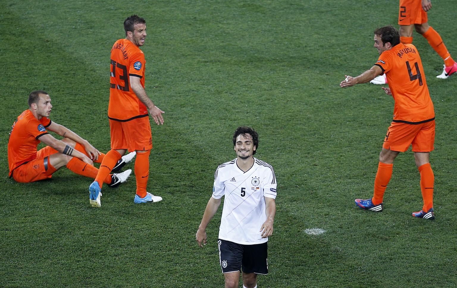 Germany's Mats Hummels smiles as Joris Mathijsen of the Netherlands, right, and Rafael van der Vaart, second left, argue during the Euro 2012 soccer championship Group B match between the Netherlands and Germany in Kharkiv, Ukraine, Wednesday, June 13, 2012. (AP Photo/Vadim Ghirda)