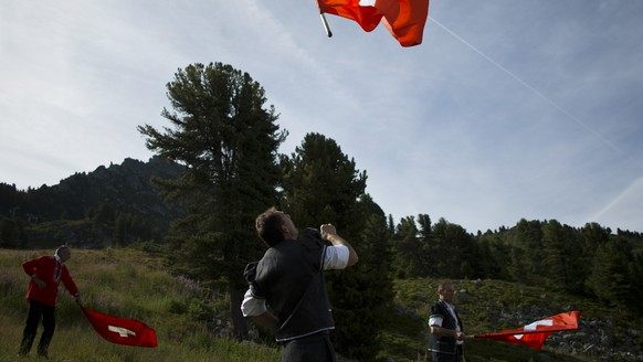 Men throw Swiss flags in the air near the Lac de Tracouet, situated 2200 meters (7220 feet) above sea level in Haute-Nendaz, canton of Valais, Switzerland, Sunday, July 26, 2015. More than 200 alpenhorn players, along with traditional flag twirlers, gathered in Nendaz on Sunday to perform as an ensemble in the Alpenhorn Festival. (AP Photo/David Azia)