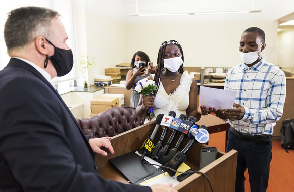 epa09360346 Newlyweds Serenity Newson (2-R) and Tyreke Punch (R), both of Queens, New York, look over their new marriage license after being married by New York City Clerk Michael McSweeney (L) in the New York City Clerk?s office during the first day of in-person weddings in the city since the start of the coronavirus pandemic last March in New York, New York, USA, 23 July 2021. Newson, who is pregnant, was heading from the wedding with her new husband to the hospital to give a scheduled birth to their son. New restrictions will allow the office to only hold 50 weddings a day which will be by appointment only.  EPA/JUSTIN LANE