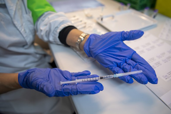 epa08922890 A nurse prepares a syringe of Pfizer-BioNTech vaccine at the m3 Sanitrade vaccination center in Geneva, Switzerland, 06 January 2021. The canton of Geneva launches its vaccination campaign against Covid-19.  EPA/MARTIAL TREZZINI