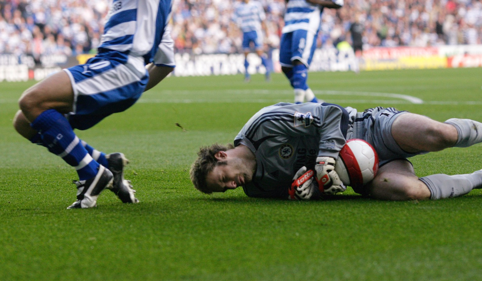 Chelsea's goalkeeper Petr Cech lies on the ground after a challenge by Reading's Stephen Hunt (L) in their English Premier League soccer match at the Madejski Stadium in Reading, southern England, October 14, 2006. NO ONLINE/INTERNET USE WITHOUT A LICENCE FROM THE FOOTBALL DATA CO LTD. FOR LICENCE ENQUIRIES PLEASE TELEPHONE +44 207 298 1656.          REUTERS/Kieran Doherty   (BRITAIN) - RTR1IBLU