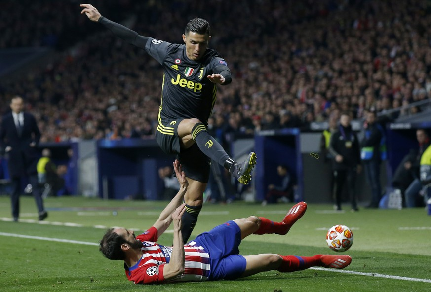 Juventus forward Cristiano Ronaldo jumps over Atletico defender Juanfran during the Champions League round of 16 first leg soccer match between Atletico Madrid and Juventus at Wanda Metropolitano stadium in Madrid, Wednesday, Feb. 20, 2019. (AP Photo/Andrea Comas)