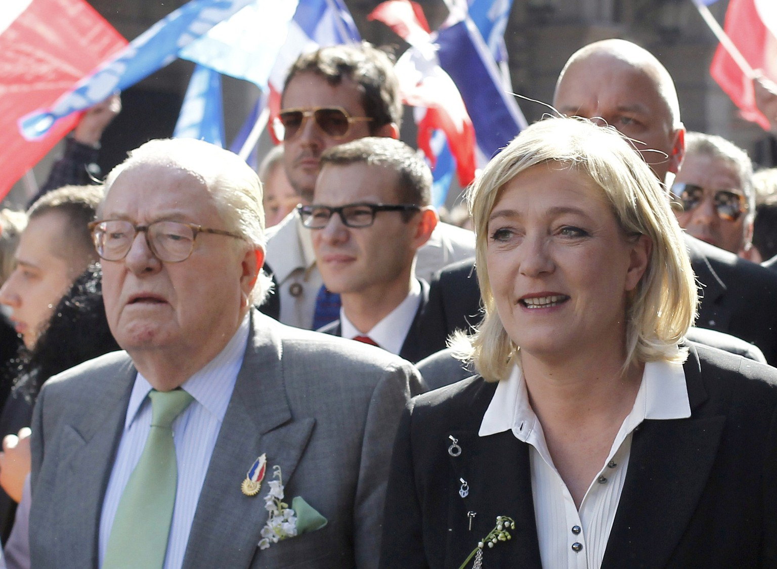 "(FILES) - A photo taken on May 1, 2012 in Paris shows French far right party Front National (FN) former presidential candidate, Marine Le Pen (R), walking near her father and former FN president Jean-Marie Le Pen (R). Anti-racism campaigners reacted with outrage on June 8, 2014 to an apparent anti-Semitic pun by France's former far-right leader Jean-Marie Le Pen that even his own party and daughter were quick to criticise. Le Pen, who has had multiple convictions for inciting racial hatred and denying crimes against humanity, once described Nazi gas chambers as a ""detail"" of history.    AFP PHOTO / THOMAS COEX"