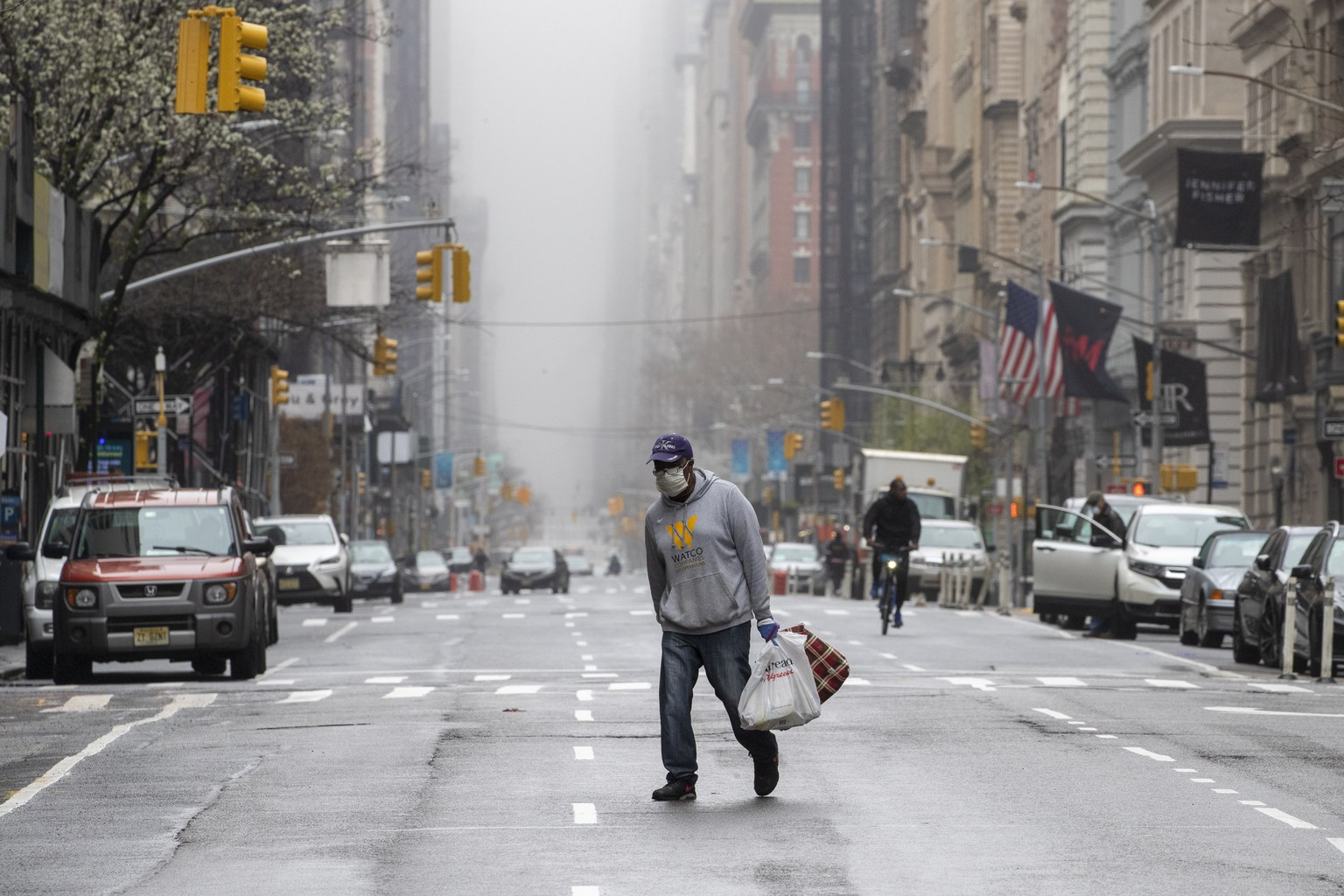 A man wearing a facial mask walks across the middle of 5th Avenue in Midtown Manhattan of New York, Sunday, March 29, 2020. (AP Photo/Mary Altaffer)