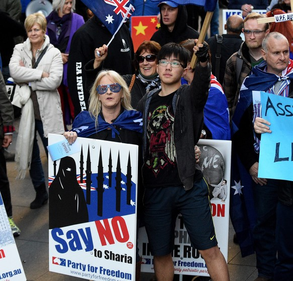 epa04852913 Protesters hold signs during a Reclaim Australia Rally at Martin Place in Sydney, Australia, 19 July 2015. Australian nationalists protesting against Islam clashed with anti-racism groups at rallies in Melbourne and Sydney.  EPA/MICK TSIKAS AUSTRALIA AND NEW ZEALAND OUT