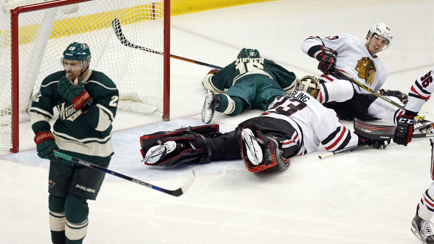 Minnesota Wild's Nino Niederreiter, left, of Switzerland, skates to the celebration, leaving Chicago Blackhawks goalie Scott Darling and Viktor Svedberg, right, of Sweden on the ice after scoring the go-ahead goal in the third period of an NHL hockey game, Friday, Oct. 30, 2015, in St. Paul, Minn. The Wild won 5-4. (AP Photo/Jim Mone)