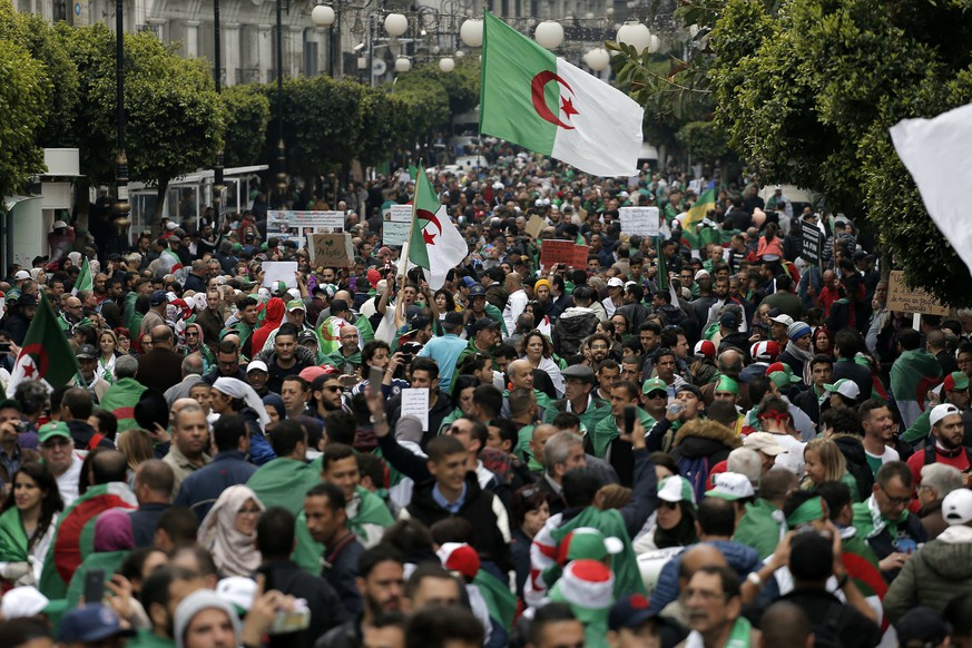 Demonstrators hold Algerian flags and chant slogans during a protest in Algiers, Algeria, Friday, May 3, 2019. Tens of thousands of Algerians protested for an 11th straight week on Friday to pressure those in power to leave, a month after long-time President Abdelaziz Bouteflika was forced to resign. (AP Photo/Toufik Doudou)