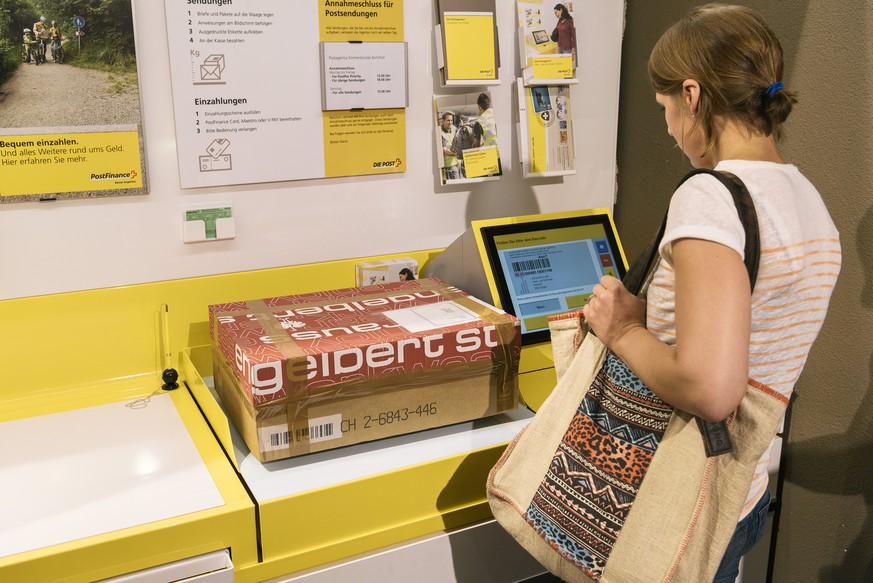 ZUR NEUAUSRICHTUNG DER POST STELLEN WIR IHNEN HEUTE, DONNERSTAG, 29. JUNI 2017, FOLGENDES NEUES BILDMATERIAL ZU POSTAGENTUREN AUS STADT, LAND UND AGGLOMERATION ZUR VERFUEGUNG --- A customer places a parcel on the scales and chooses the postage stamp on a monitor, pictured at a postal agency of the Swiss Post in an Avec shop in Emmenbruecke, Canton of Lucerne, Switzerland, on June 20, 2017. (KEYSTONE/Christian Beutler)