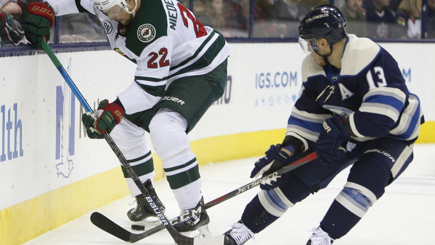 Minnesota Wild's Nino Niederreiter, left, of Switzerland, and Columbus Blue Jackets' Cam Atkinson vie the the puck during the first period of an NHL hockey game Thursday, Nov. 29, 2018, in Columbus, Ohio. (AP Photo/Jay LaPrete)