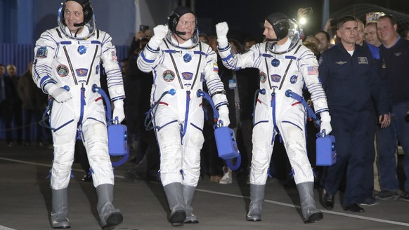 Russian cosmonaut Oleg Artemyev, centre, U.S. astronauts Richard Arnold, right, and Andrew Feustel, members of the main crew of the expedition to the International Space Station (ISS), walk to report to members of the State Committee prior the launch of Soyuz MS-08 space ship at the Russian leased Baikonur cosmodrome, Kazakhstan, Wednesday, March 21, 2018. (AP Photo/Dmitri Lovetsky, pool)