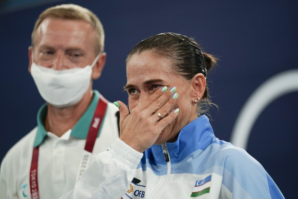 Oksana Chusovitina, of Uzbekistan, wipes away a tear after competing in vault during the women's artistic gymnastic qualifications at the 2020 Summer Olympics, Sunday, July 25, 2021, in Tokyo, Japan. (AP Photo/Ashley Landis)