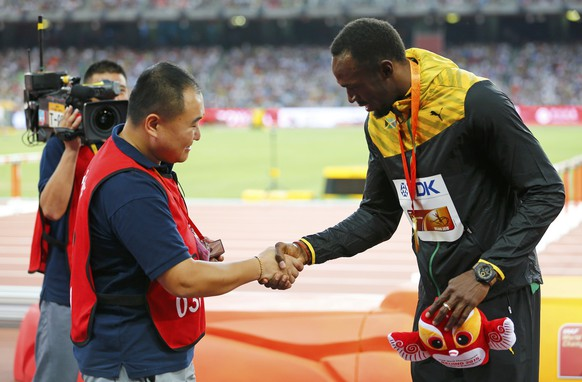 Usain Bolt of Jamaica (R), gold medalist, shakes hands with Song Tao, a cameraman of CCTV, whose Segway lost control and hit Bolt, after the podium ceremony for the men's 200 metres event during the 15th IAAF World Championships at the National Stadium in Beijing, China, August 28, 2015.         REUTERS/Damir Sagolj  TPX IMAGES OF THE DAY
