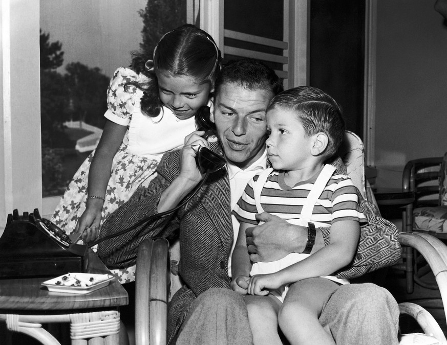 In this 1948 file photo, Frank Sinatra holds a telephone with his children, Nancy and Frank Jr., in the Hollywood area of Los Angeles. Frank Sinatra Jr., who carried on his famous father's legacy with his own music career, died unexpectedly of cardiac arrest while on tour Wednesday, March 16, 2016, his family said. He was 72. (AP Photo)