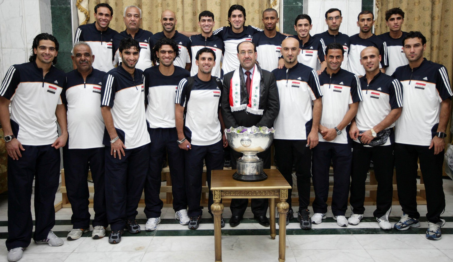 In this image released by the Iraqi government, Prime Minister Nouri al-Maliki, center, stands with the Iraqi national soccer team, at a celebration for their Asian Cup victory in the heavily-fortified Green Zone in Baghdad, Iraq, on Friday, Aug. 3, 2007. (AP Photo/Iraqi Government, HO)