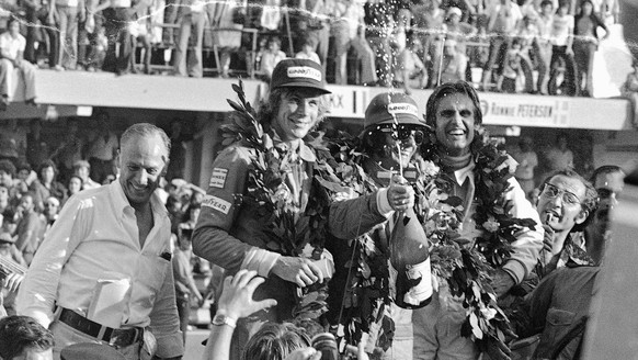 Brazil's Emerson Fittipaldi (center) sprays champagne in the winners platform after the Argentine Grand Prix in Buenos Aires, Argentina on Jan. 12, 1975. Fittipaldi was flanked by James Hunt (left) who was second and Carlos Reutemann, right, third. (KEYSTONE/AP Photo/E Di Baia)