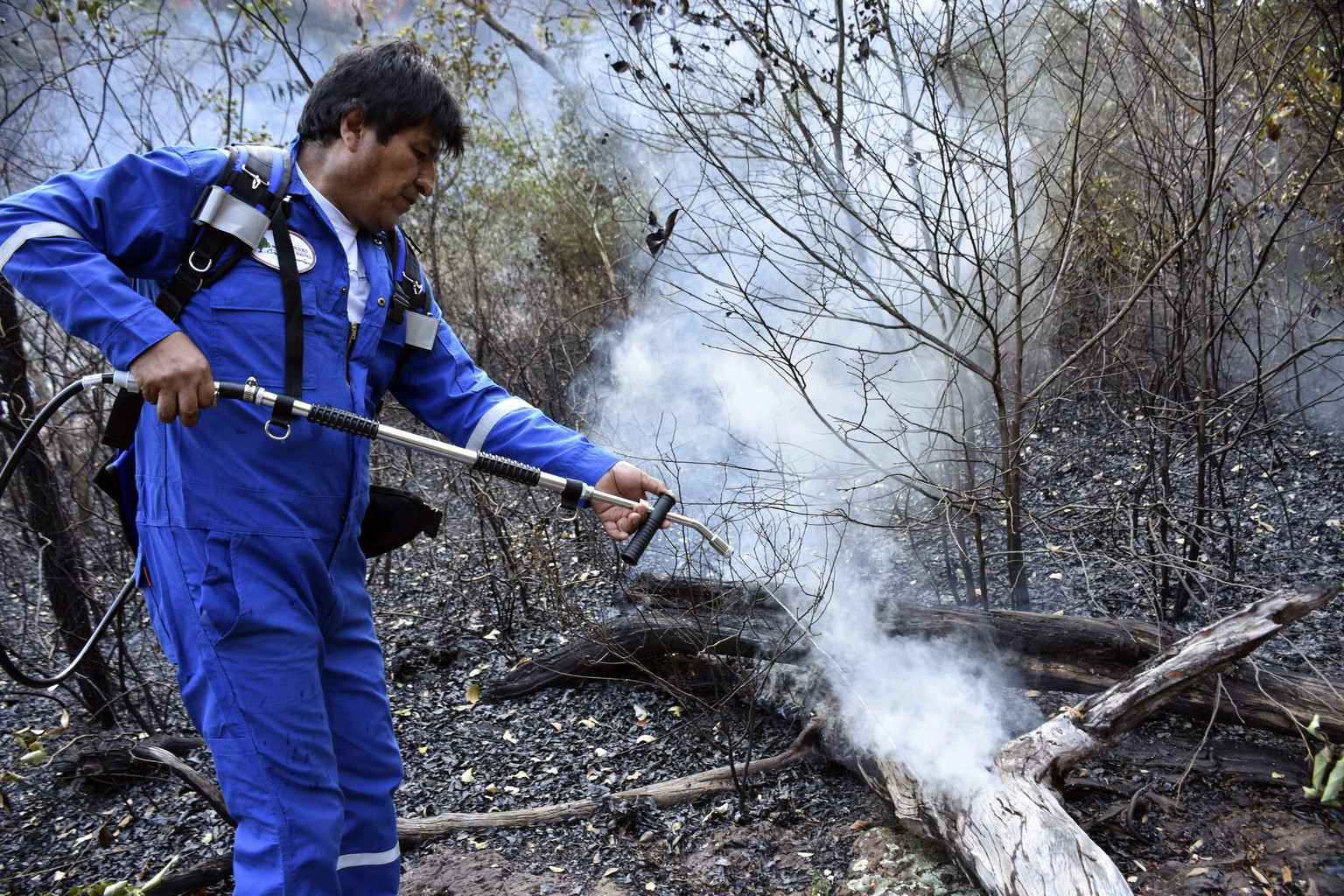 In this photo courtesy of Bolivia's Communication Ministry press office, Bolivian President Evo Morales sprays water at a fire on the outskirts of Robore, Bolivia, Tuesday, Aug. 27, 2019. Morales, who has been under criticism for an allegedly slow response to the fires, issued a decree in July allowing controlled burns and clearing of lands, after granting amnesty last year to people caught burning fields illegally. (Raul Martinez/Bolivia's Communication Ministry press office via AP)