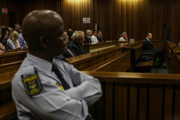 Oscar Pistorius, right, sits in the dock and listens to cross questioning about the events surrounding the shooting death of his girlfriend Reeva Steenkamp, in court during his trial in Pretoria, South Africa, Tuesday, March 11, 2014. Pistorius is charged with the shooting death of Steenkamp, on Valentines Day in 2013. (AP Photo/Kevin Sutherland, Pool)