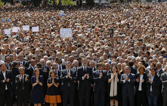 King Felipe of Spain, center, Prime Minister Mariano Rajoy, center left, and Catalonia regional President Carles Puigdemont, center right, join people gathered for a minute of silence in memory of the terrorist attacks victims in Las Ramblas, Barcelona, Spain, Friday, Aug. 18, 2017. Spanish police on Friday shot and killed five people carrying bomb belts who were connected to the Barcelona van attack that killed at least 13, as the manhunt intensified for the perpetrators of Europe's latest rampage claimed by the Islamic State group. (AP Photo/Francisco Seco)