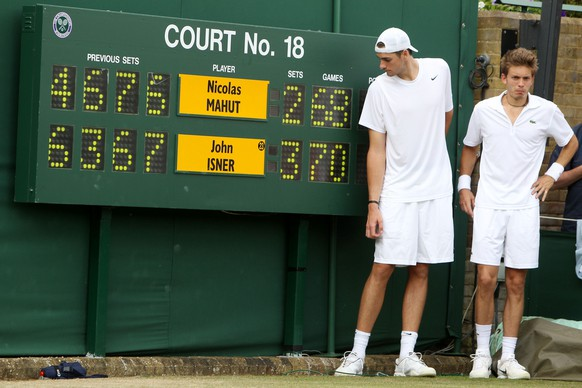 FILE - This June 24, 2010, file photo shows John Isner of the U.S. and France's Nicolas Mahut, right, posing for a photo next to the scoreboard following their record-breaking men's singles match at the All England Lawn Tennis Championships at Wimbledon. No other match had lasted longer than 6 hours, 33 minutes, a time Isner and Mahut surpassed by more than 4œ hours. No other match had lasted more than 112 games; they played 183. The fifth set alone lasted 138 games over 8 hours, 11 minutes. (AP Photo/Alastair Grant, File Pool)