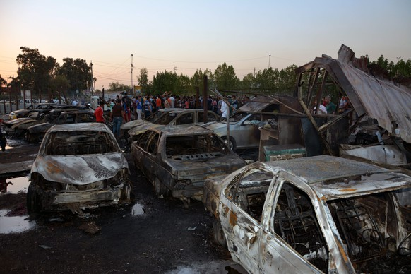 epa04885209  Iraqis inspect the site of a car bomb attack in Habibiya district, northeast of Baghdad, Iraq, 15 August 2015.  At least 10 people were killed when a car bomb went off in a mostly Shiite area of Baghdad, police said. At least 18 others were wounded in the bombing at a site housing car showrooms in the Sadr City area of eastern Baghdad, they added.  EPA/MOHAMMED JALIL