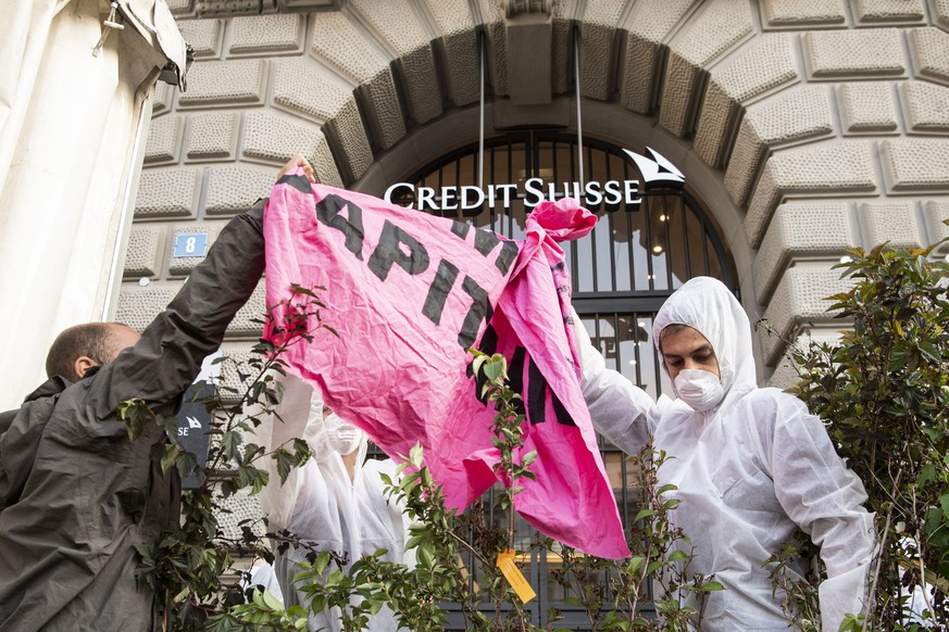 A group of climate activists from the Collective Climate Justice organization is blocking the entrance to the Swiss bank Credit Suisse on Paradeplatz in Zurich, Switzerland, Monday, July 8, 2019. The activists demonstrate against the trade with fossil fuels. (Ennio Leanza/Keystone via AP)