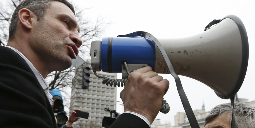 Ukrainian opposition leader and head of the UDAR (Punch) party Vitaly Klitschko (L) holds a loud-speaker as he addresses anti-government protesters outside the Ukrainian Parliament building in Kiev February 22, 2014. The heads of four Ukrainian security bodies, including the police's Berkut anti-riot units, appeared in parliament on Saturday and declared they would not take part in any conflict with the people. REUTERS/Vasily Fedosenko (UKRAINE - Tags: POLITICS CIVIL UNREST)
