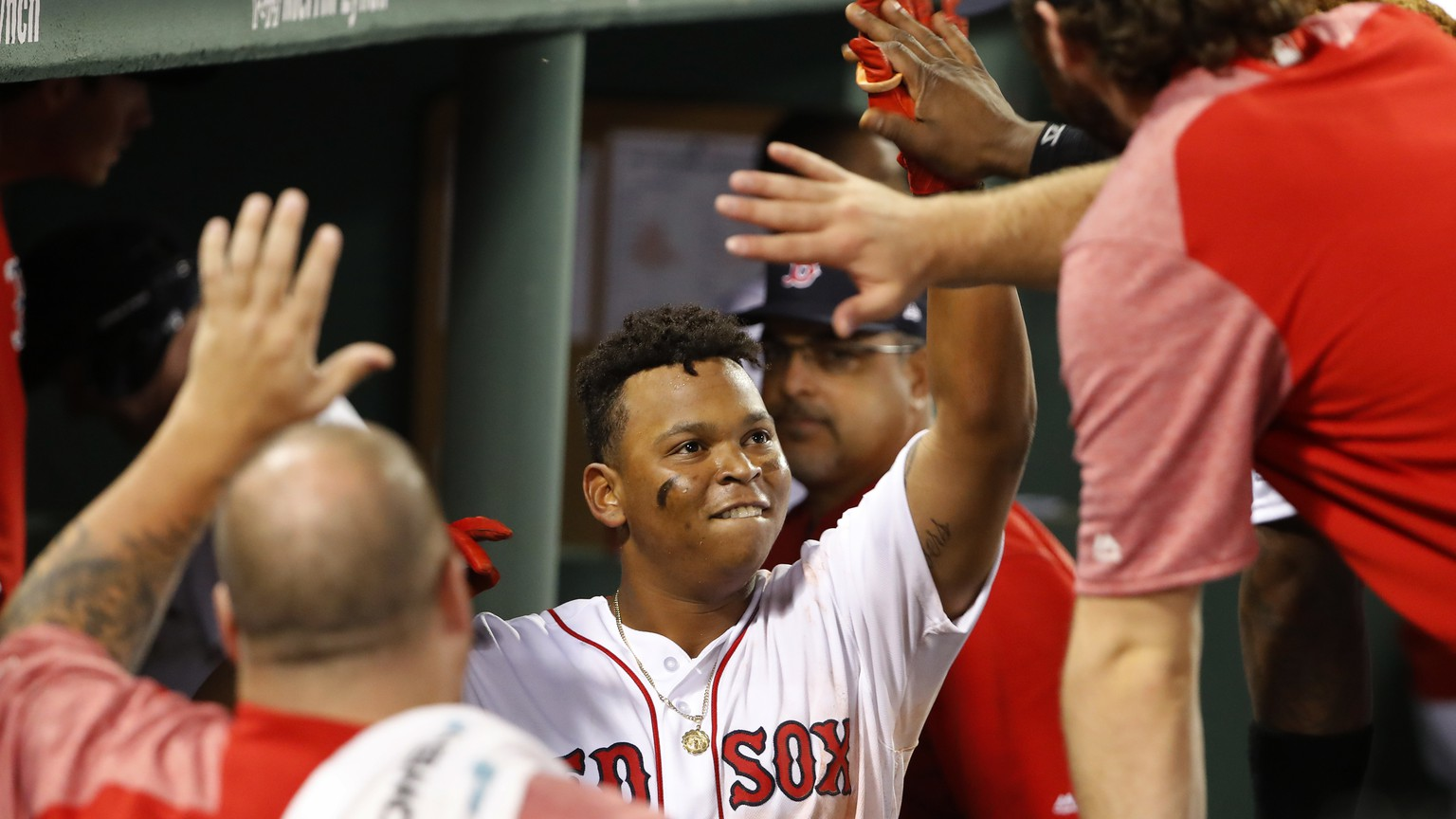 Boston Red Sox's Rafael Devers is congratulated in the dugout after his home run against the New York Yankees during the seventh inning of a baseball game at Fenway Park in Boston on Saturday, Aug. 19, 2017. (AP Photo/Winslow Townson)