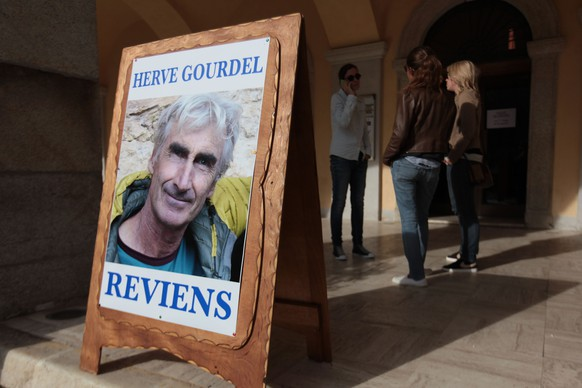 This picture taken on September 23, 2014 shows a poster depicting Herve Gourdel, 55, a mountain guide who was seized on September 21 evening while trekking in the rugged, heavily forested Kabylie area, where Al-Qaeda is active, and reading