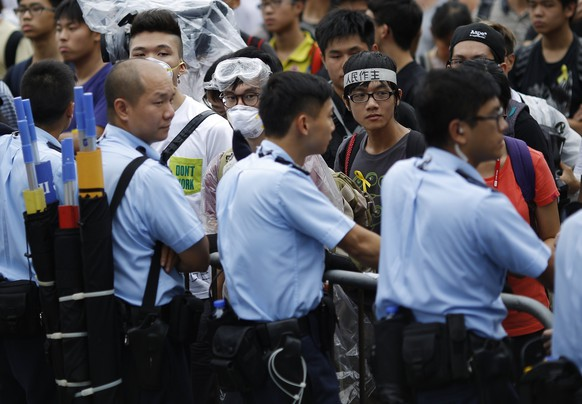 Police officers stand as protesters block the entrance to Hong Kong's Chief Executive Leung Chun-ying offices in Hong Kong, October 2, 2014.  Hong Kong's leader is willing to let pro-democracy demonstrations blocking large areas of the city go on for weeks if necessary, a source close to him said, while defiant protesters vowed they would not budge. REUTERS/Carlos Barria (CHINA - Tags: CIVIL UNREST POLITICS)