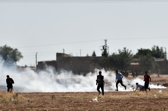 Kurds run  from tear gas as the Turkish army removes them from the village of Mursitpinar next to the Syrian town of Ain al-Arab, known as Kobane by the Kurds, on the Turkish-Syrian border on October 6, 2014. Turkish security forces on Monday used tear gas to push dozens of reporters and Kurdish civilians away from the border zone close to intense fighting for the besieged Syrian town of Kobane. AFP PHOTO / ARIS MESSINIS