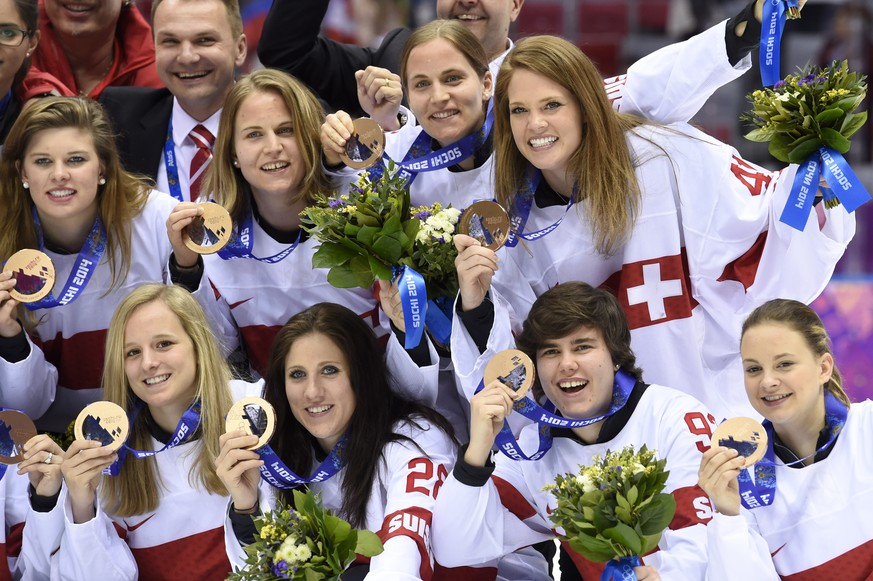 Switzerland's ice hockey women goalkeeper Florence Schelling, right up, and teamates celebrate their bronze medal during the women's ice hockey victory ceremony at the XXII Winter Olympics 2014 Sochi, at the Bolshoy Ice Dome, in Sochi, Russia, on Thursday, February 20, 2014. (KEYSTONE/Laurent Gillieron)