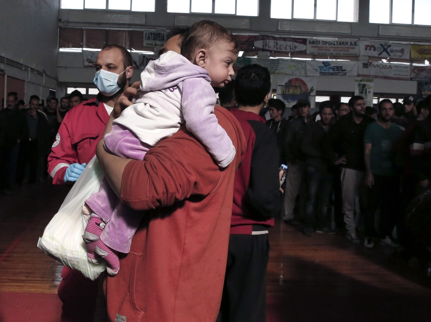 Immigrants who arrived on a cargo ship from Turkey queue for meals in a basketball arena where they have been given temporary shelter in the town of Ierapetra, on the southern Greek island of Crete on Friday, Nov. 28, 2014. Nearly 600 men, women and children, mostly refugees from Syria, have been temporarily put up in the southern Cretan town of Ierapetra, where they arrived in a crippled smuggling ship after more than a week at sea. (AP Photo/Petros Giannakouris)