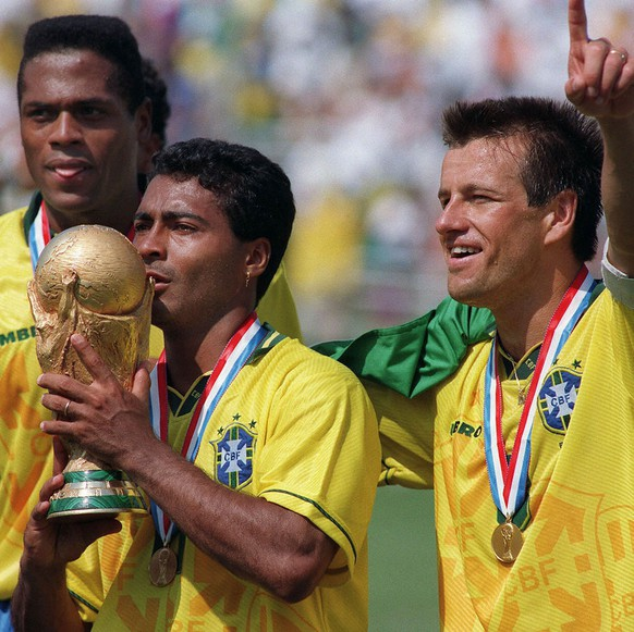 Brazilian forward Romario kisses the FIFA World Cup trophy, flanked by Ronaldao (L) and captain Dunga, after Brazil defeated Italy 3-2 in the shoot-out session at the end of the World Cup final, 17 July 1994 at the Rose Bowl in Pasadena.  (KEYSTONE/EPA PHOTO/AFP/Daniel Garcia)