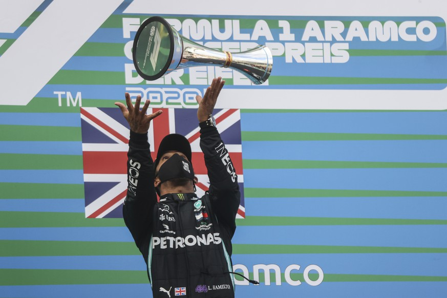 Mercedes driver Lewis Hamilton of Britain launches the trophy in the air on the podium after winning the Eifel Formula One Grand Prix at the Nuerburgring racetrack in Nuerburg, Germany, Sunday, Oct. 11, 2020. (Wolfgang Rattay, Pool via AP)
