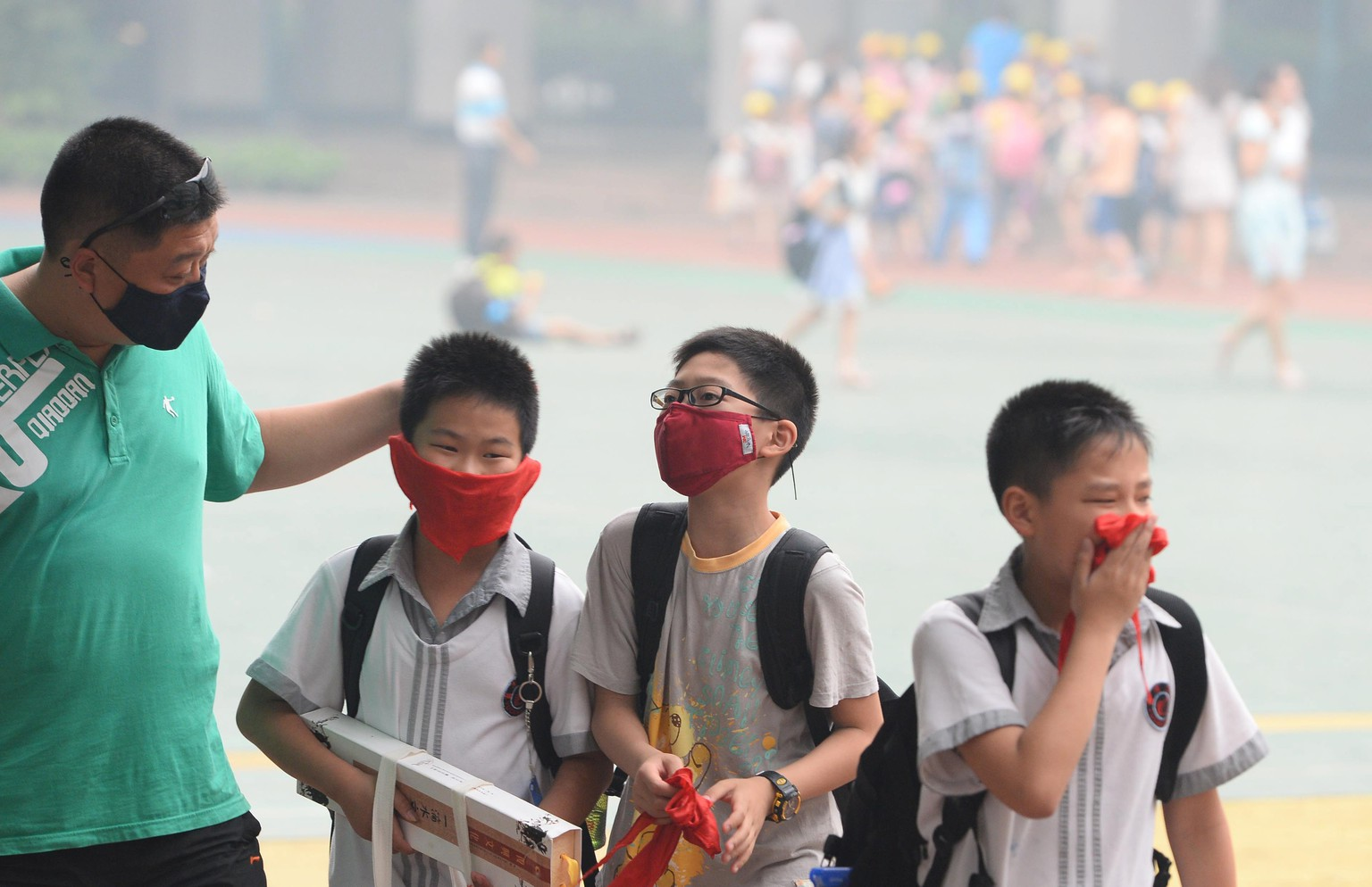 WUHAN, CHINA - JUNE 12: (CHINA OUT) A man with three students wear breath mask at the haze shrouded Hankou district on June 12, 2014 in Wuhan, Hubei province of China. Haze shrouded China,'s southeast city Wuhan on June 12 and the air quality index at 6pm reached 410. (Photo by ChinaFotoPress)***_*** (FOTO: DUKAS/CHINAFOTOPRESS)