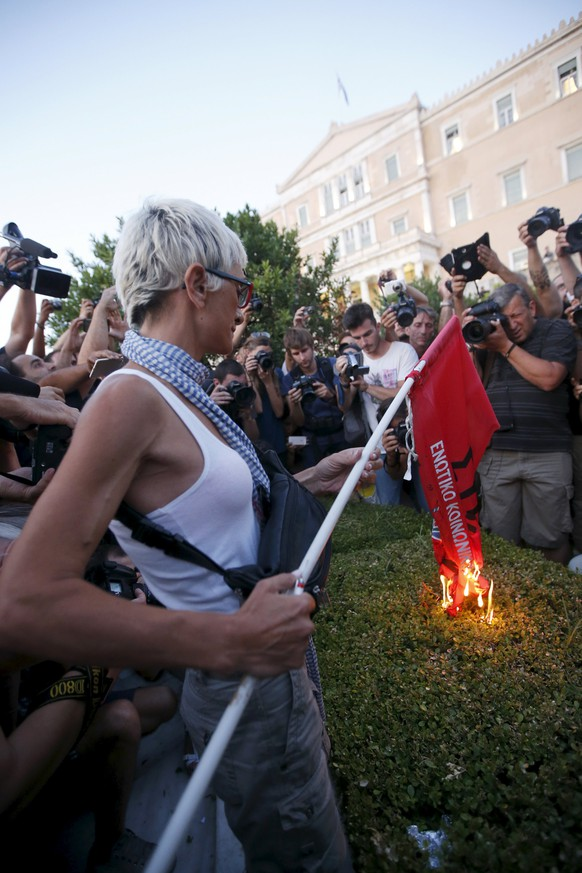 An anti-EU protester burns a leftist Syriza ruling party flag during a demonstration of about five hundred people in front of the parliament building in Athens, Greece July 13, 2015. Euro zone leaders made Greece surrender much of its sovereignty to outside supervision on Monday in return for agreeing to talks on an 86 billion euros bailout to keep the near-bankrupt country in the single currency.   REUTERS/Jean-Paul Pelissier
