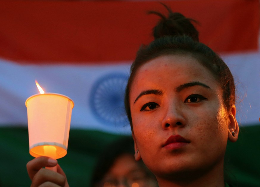 epa06677631 A Member of the Northeast People Voice India Foundation, a non-governmental organization, holds a candle in front of Indian tri colour flag during a candle light vigil as they condemned and call for justice in the rape and murder case of an eight-year-old nomadic girl, in Bangalore, India, 18 April 2018. Hundreds of people gathered and staged a protest to bring attention to rape cases and violence against women in India after a girl child was gang raped and murdered in Kathua district of Jammu region in January 2018. Protesters demanded justice for the victim and action against the accused. The Crime Branch of Jammu and Kashmir Police has filed a charge sheet of the case in a local court and indicted eight people in the case.  EPA/JAGADEESH NV