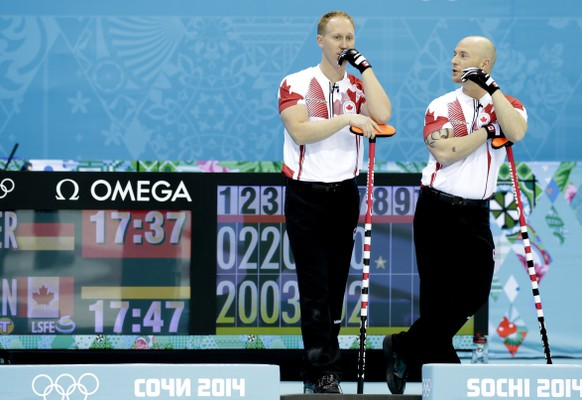 Canada's skip, Brad Jacobs, left, and Ryan Fry, right, discuss tactics during the men's curling competition against Germany at the 2014 Winter Olympics, Monday, Feb. 10, 2014, in Sochi, Russia. (AP Photo/Wong Maye-E)