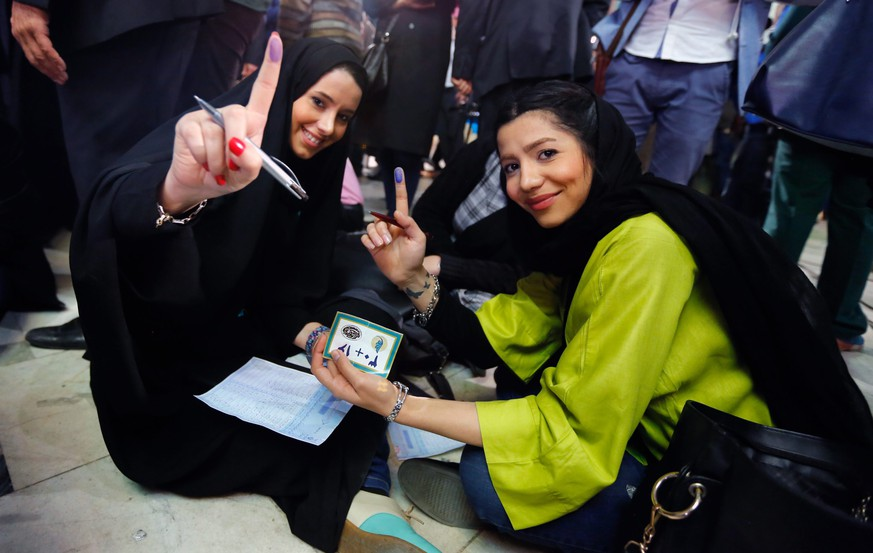 epa05182231 Iranians girls show their inked fingers as they sit on the floor filling their ballot in last minute of voting time for the parliamentary and Experts Assembly election at a polling station at Ershad Mosque in Tehran, Iran, 26 February 2016. Nearly 55 million voters will elect on 26 February the representatives out of 6,229 candidates competing for 290 parliamentary seats, in addition to choosing 88 members out of 161 clerics for the Assembly of Experts, the body responsible for electing a new supreme leader in case the post becomes vacant.  EPA/ABEDIN TAHERKENAREH